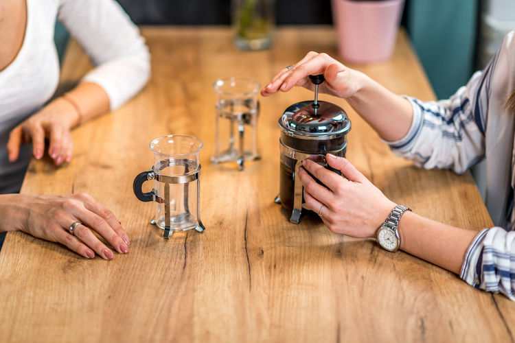 Girlfriends Having Coffee Together Coffee French Press Females Women Cafe Home Drink Young Girl Cup Hot Glass Two People Enjoy People Caucasian Happy Lifestyle Concept Caffeine Indoors  Holding Beautiful Adult Casual Enjoyment Break Table Aroma Woman Close Up Drinking Happiness French Press Coffee Wooden Table Hands Indoors  Sitting Food And Drink