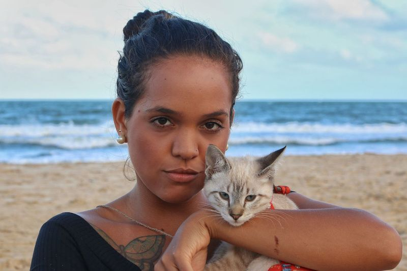 Portrait of young woman with cat on beach