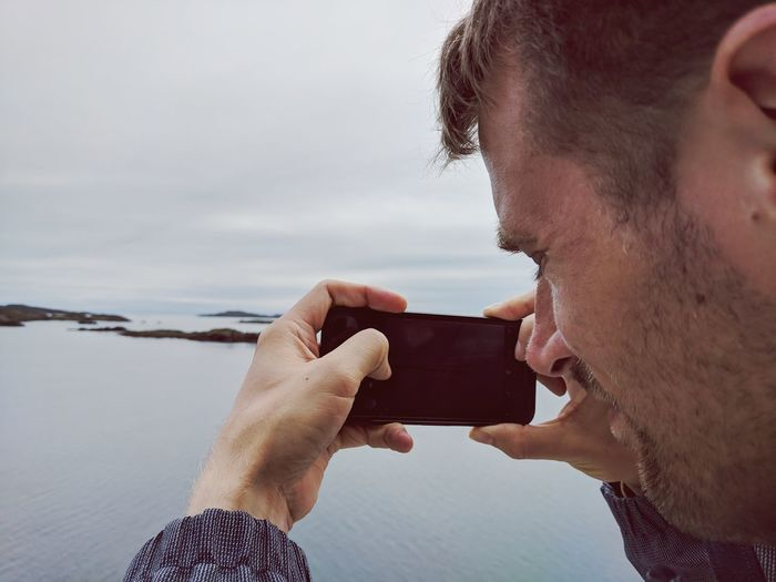 Side View Of Mid Adult Man Photographing Sea With Smart Phone While Standing Against Cloudy Sky