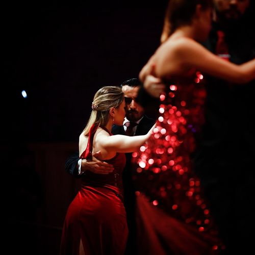 Adult Black Background Couple - Relationship Dancing Embracing Emotion Falling In Love Heterosexual Couple Love Men Night Nightlife Positive Emotion Red Romance Three Quarter Length Togetherness Two People Women Young Adult Young Couple Young Men Young Women