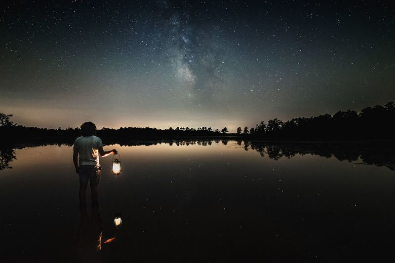 A still summer evening illuminated by nothing but lamplight and the stars - the ultimate therapy. Constellation Nature Silhouette Milky Way One Man Only Galaxy Beauty In Nature Men Star Field Lake Sky Real People Reflection Astrophotography New Jersey