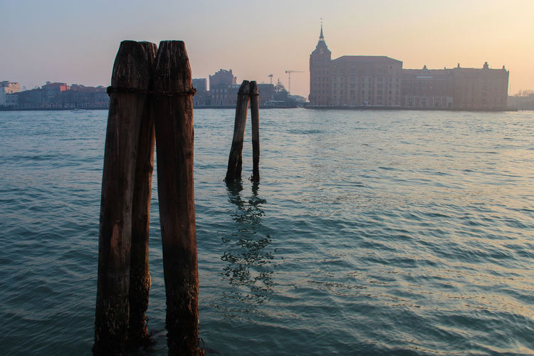 Scenic view of la giudecca with wooden posts at sunset