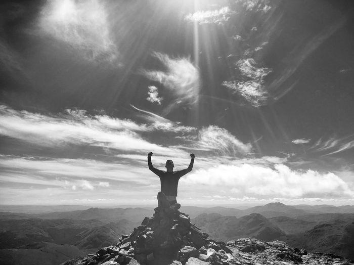 Man Sitting On Mountain Peak Against Sky