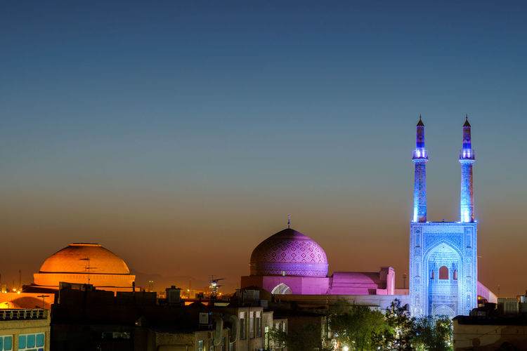 Illuminated mosque against sky during sunset