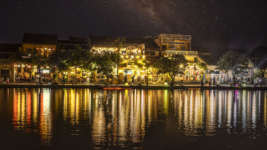 Illuminated buildings by lake against sky in city at night