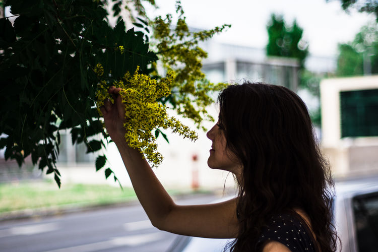 Side view of woman smelling flowers