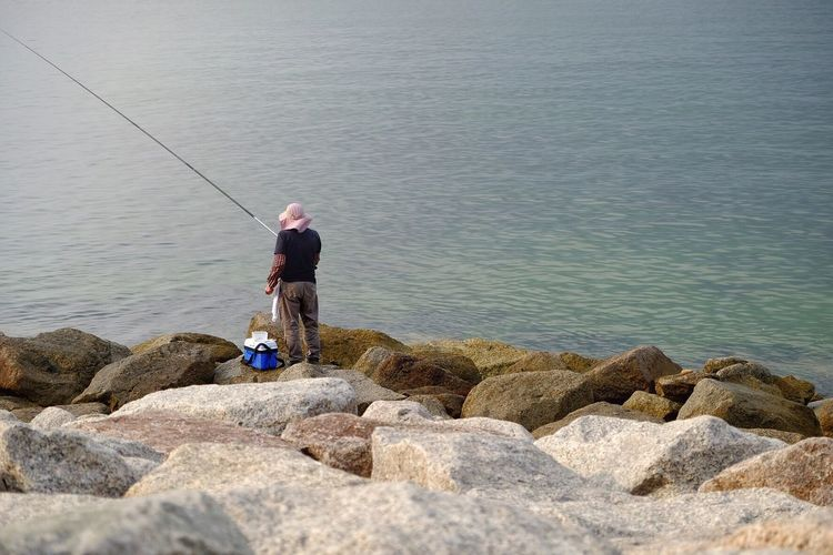 Rear View Of Man Fishing At Rocky Shore