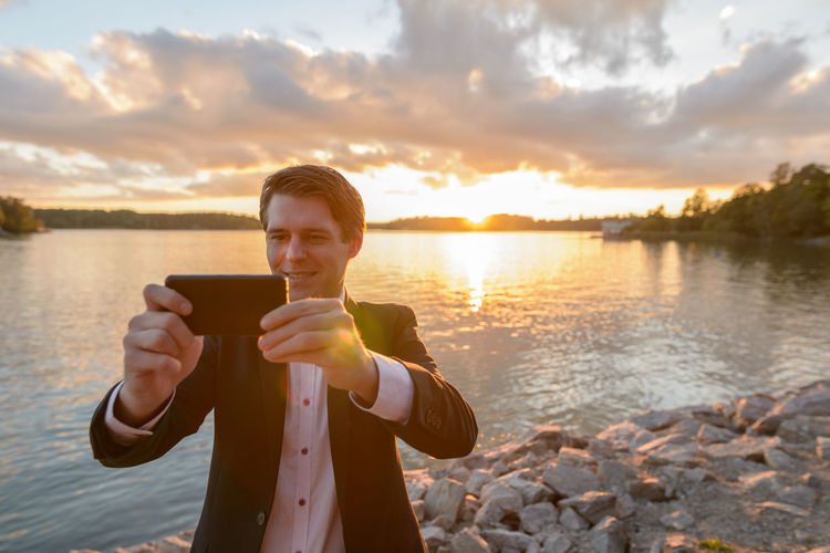 Full length of man photographing while using phone against sky during sunset