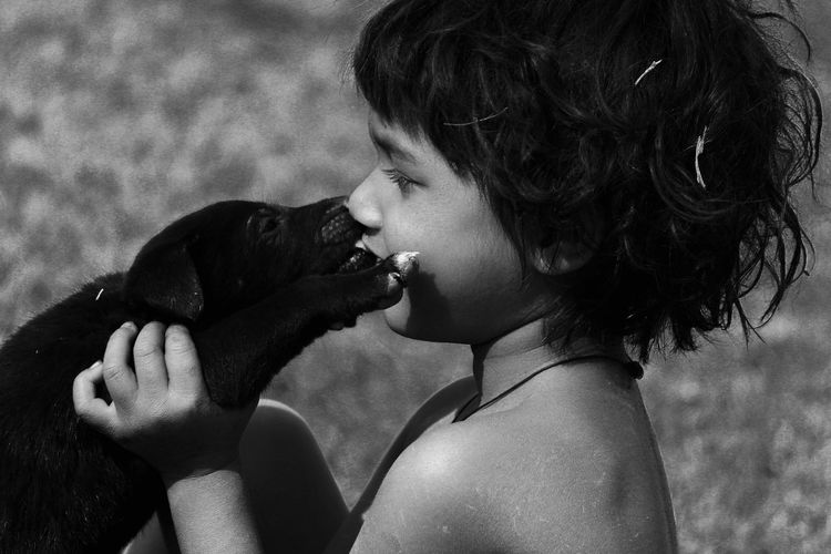 Side view of cute girl kissing dog