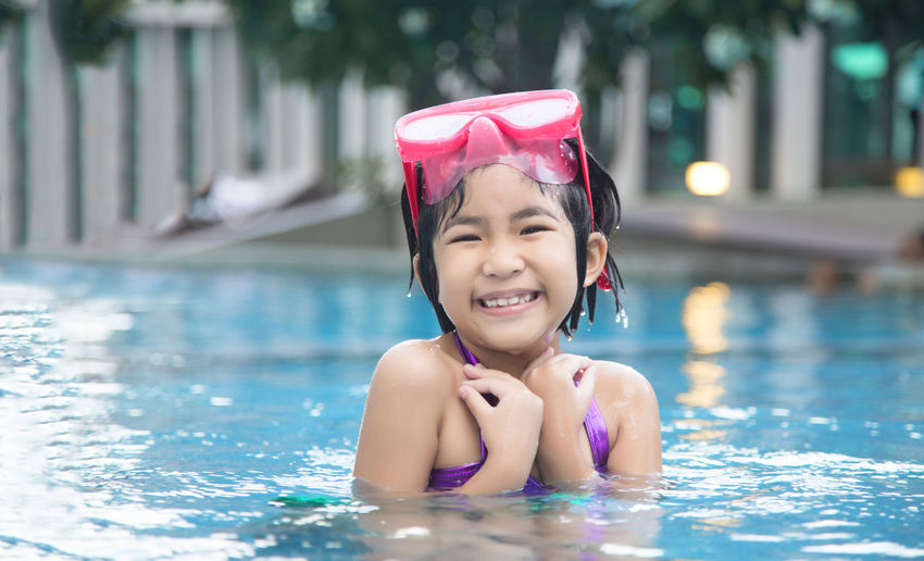 Happy asian kid big smile to playing swim in water pool at summer