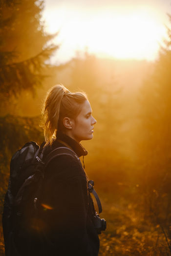 Side view of woman standing in forest during sunset