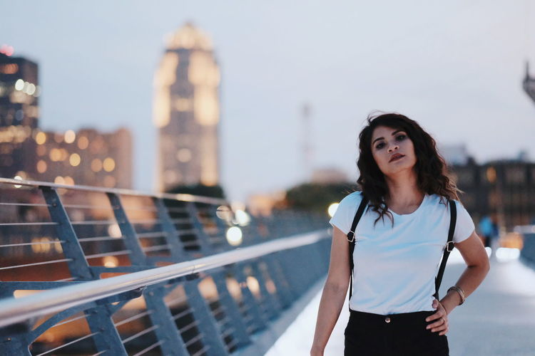 Portrait of woman standing on bridge in city at dusk