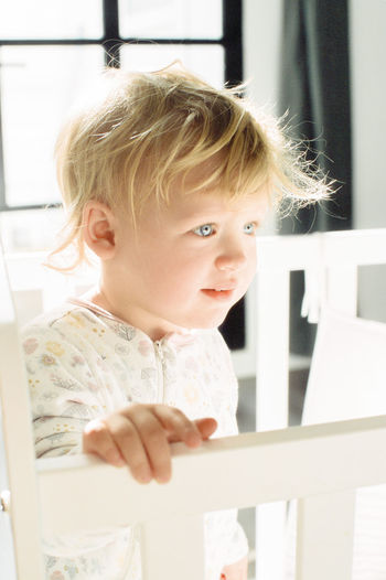Cute baby girl looking away in crib at home
