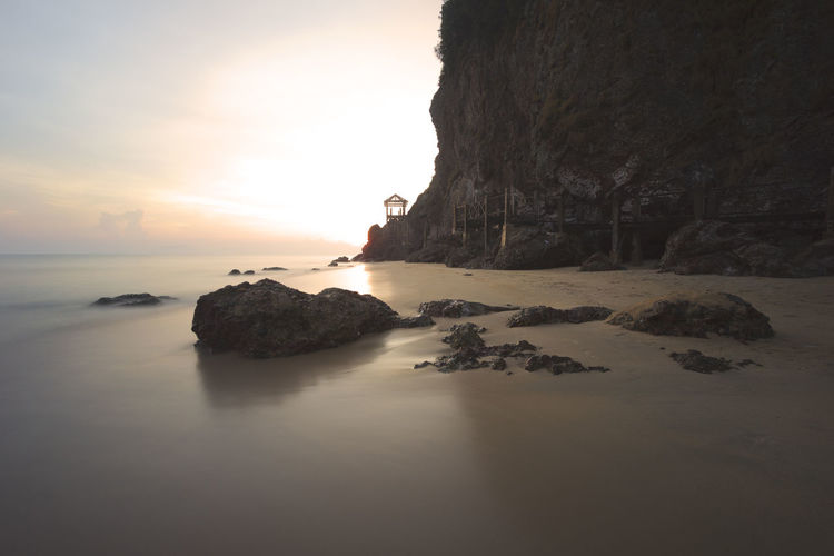 Beautiful location for tourism. The shot was captured with long exposure. Beauty In Nature Cliff Day Horizon Over Water Nature No People Outdoors Rock - Object Rock Formation Scenics Sea Sea, Travel, Summer, Beach, Tropical, Vacation, Ocean, Water, Sand, Holiday, Sun, Sky, Beautiful, Fun, Resort, People, Tourism, Freedom, Tree, Palm, Nature, Island, Paradise, Seascape, Trip, Calm, Landscape, Tropics, Concept, Day, Coast, Bright, Traveler, Sky Sunset Tranquil Scene Tranquility Water