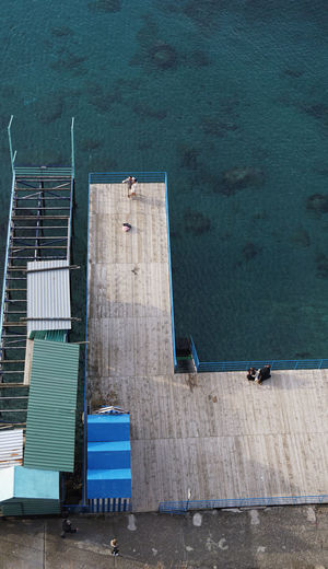 High Angle View Of Couple Standing On Pier At Sea