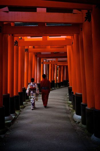 Rear View Of Man And Woman Walking Under Torii Gate