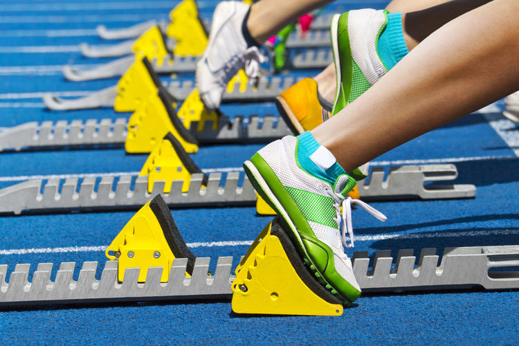Low section of people standing by track starting blocks
