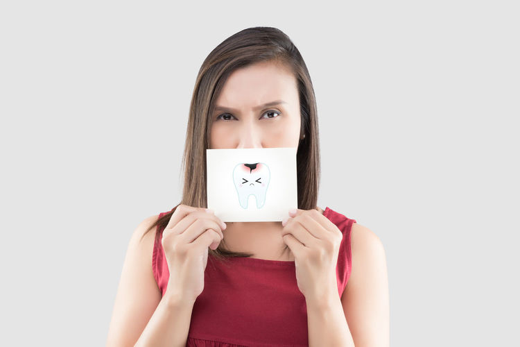 Asian woman in the red shirt holding a white paper with the caries cartoon picture of his mouth against the gray background, Have a toothache, The concept with healthcare gums and teeth Dental Ache Cavities Teeth Decay Pain Tooth Toothache Caries Caries Dental