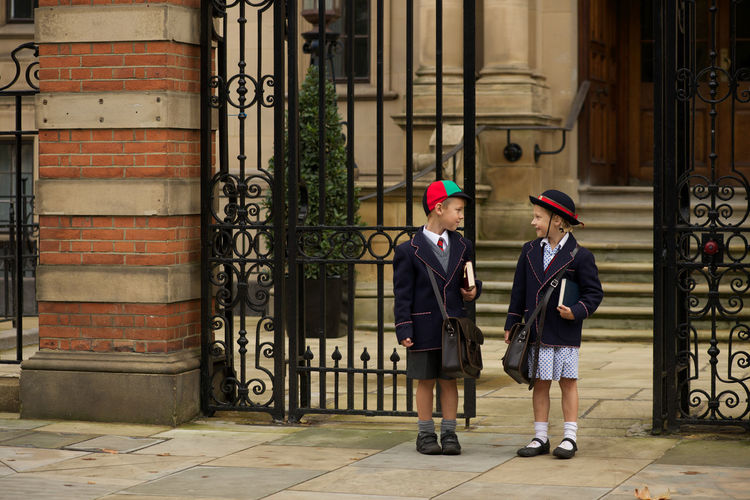 Boy and girl standing by school gate