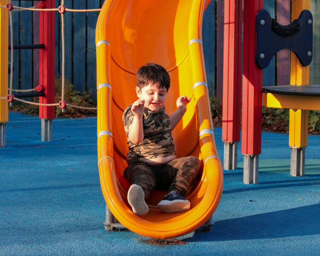 Boy sitting on slide at playground