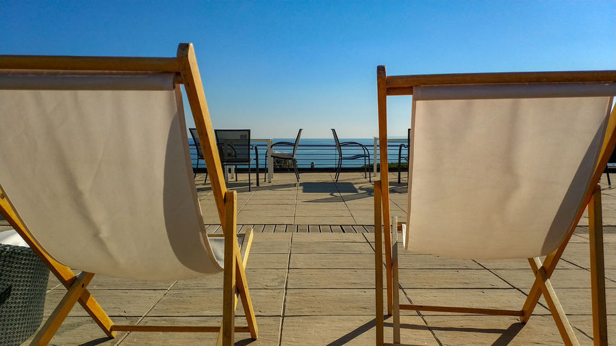 Empty chairs by sea against clear blue sky