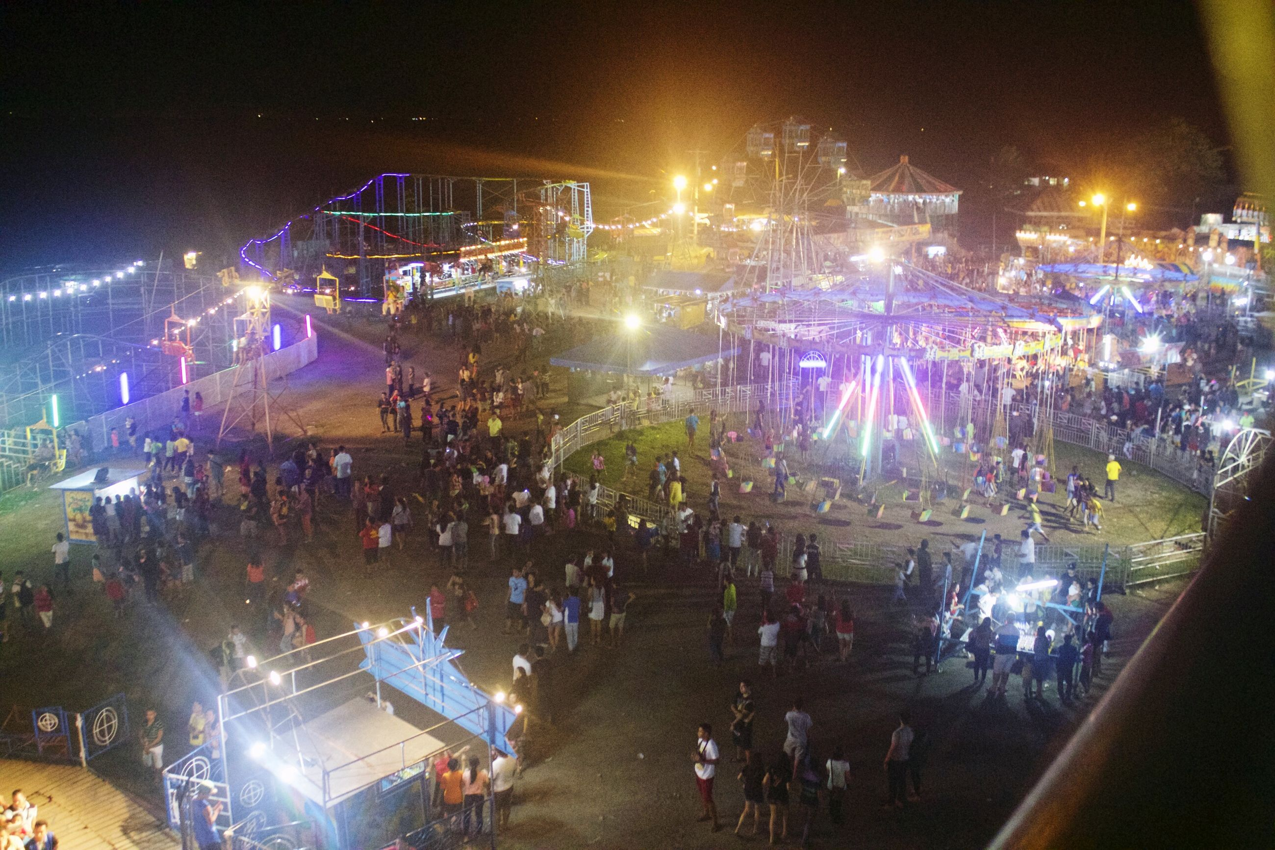 illuminated, night, large group of people, city, building exterior, lighting equipment, light - natural phenomenon, city life, lifestyles, sky, leisure activity, architecture, street light, built structure, crowd, light beam, high angle view, glowing, enjoyment