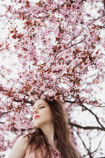Portrait of woman with pink cherry blossoms in spring