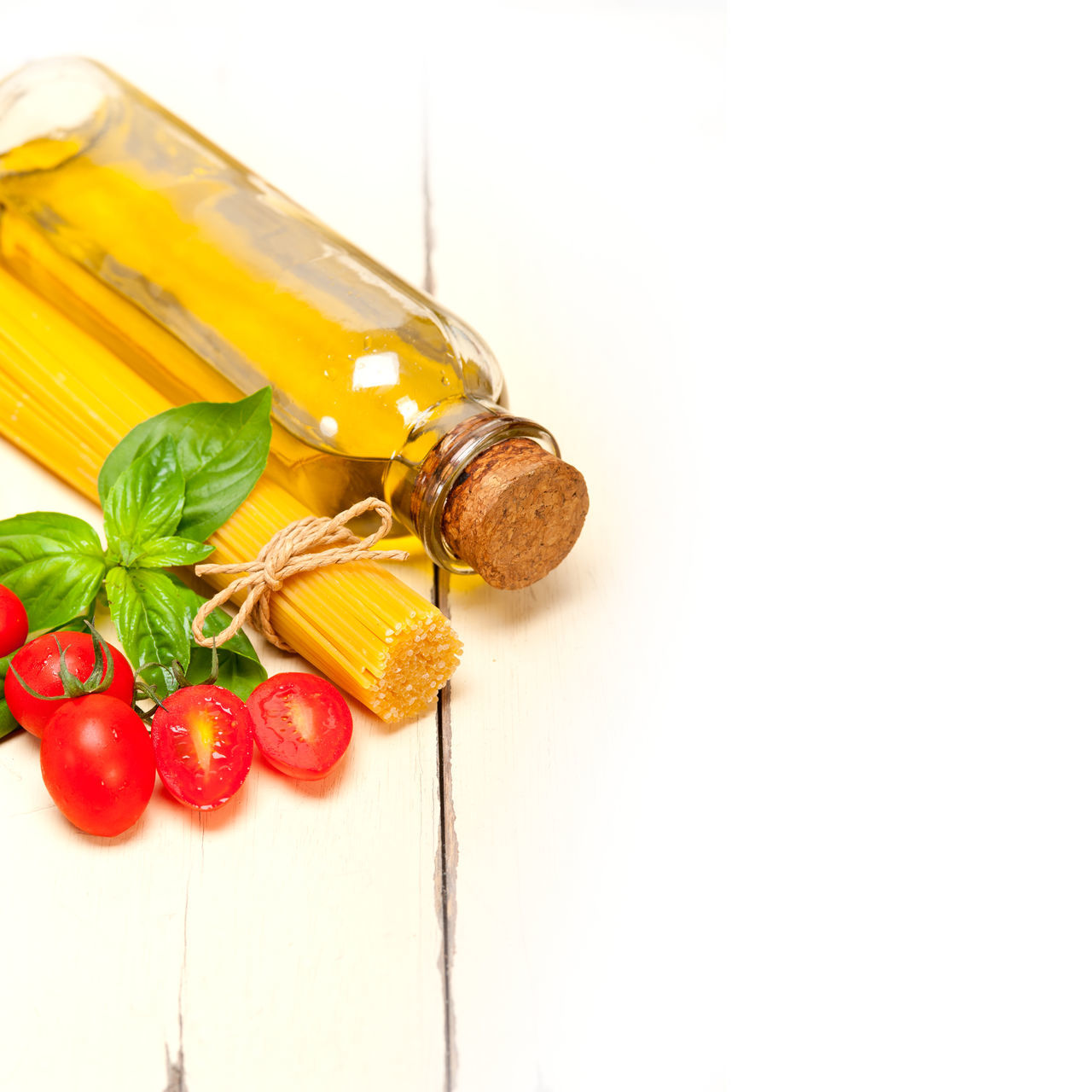 Close-Up Of Tied Spaghetti With Tomatoes And Bottle On Table