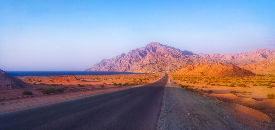 Country road amidst desert against sky