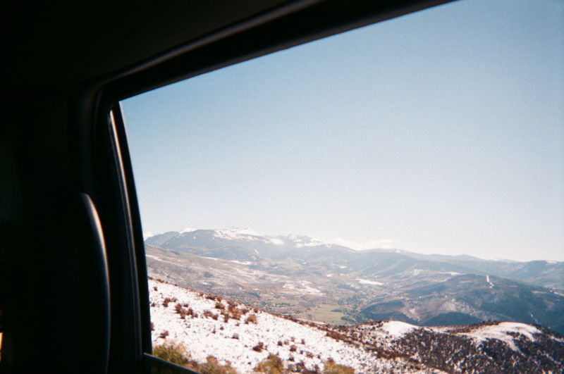 Scenic view of mountains against clear sky seen through window