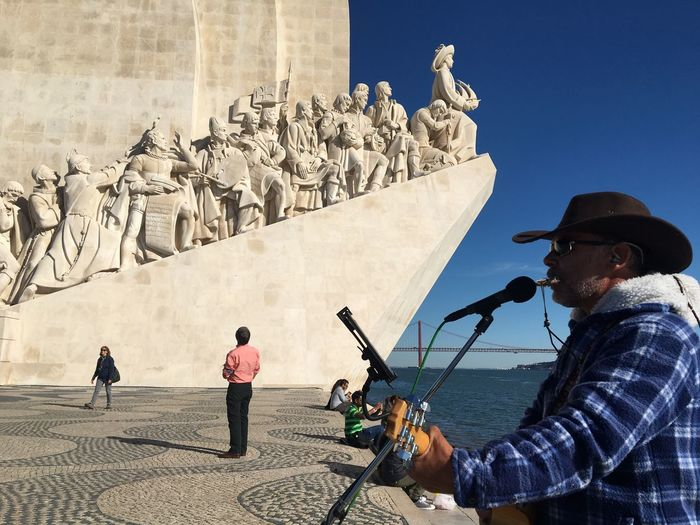A man in cowboy hat sings a country song near the Padrão dos Descobrimentos (Monument to the Discoveries) in Belem district, west of the capital Lisbon. The monument was built to commemorate the 500th anniversary of the death of Henry the Navigator and to honour Portuguese explorers. Art And Craft History Travel Destinations Sculpture Outdoors Statue Men Real People Day Sky Adult People Portugal Lisbon Belém Padrão Dos Descobrimentos Eyeemportugal EyeEmlisboa