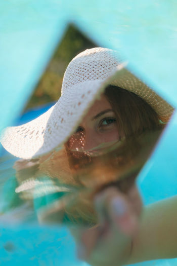 Close-up of young woman holding mirror with reflection in wading pool