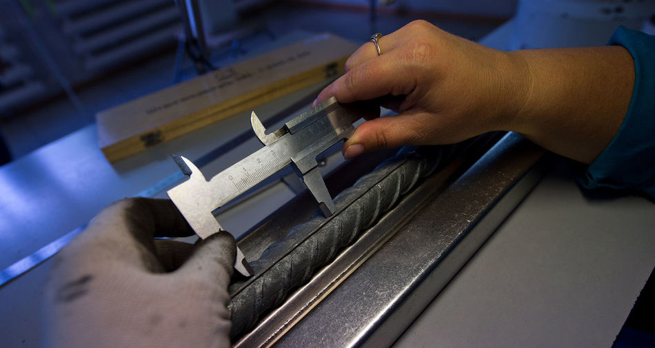 Cropped image of hands using vernier calliper in workshop