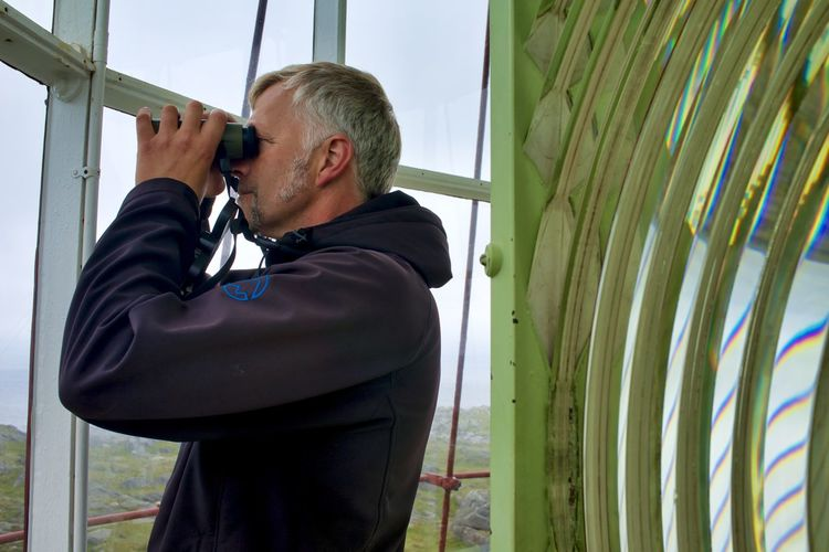 Norway, Utsira: man watching through binocular from inside a lighthouse; lighthouse keeper Horizontal Day Adult Binoculars White Hair Grey Hair Gray Hair Looking Watching Profile Portrait Caucasian Hand Hood - Clothing Lighthouse Lighthouse Keeper One Person Real People Men Standing Waist Up Lifestyles Technology Casual Clothing Males  Leisure Activity Outdoors Side View Occupation