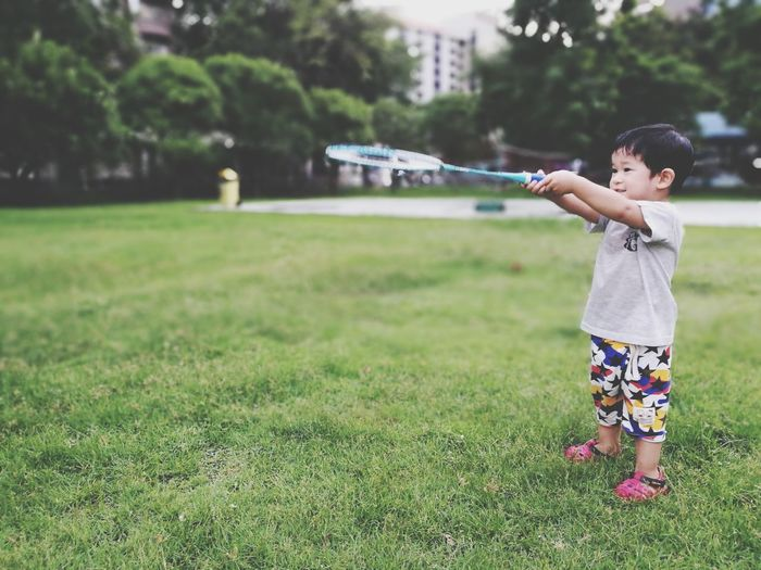 Boy playing with racket on field in park