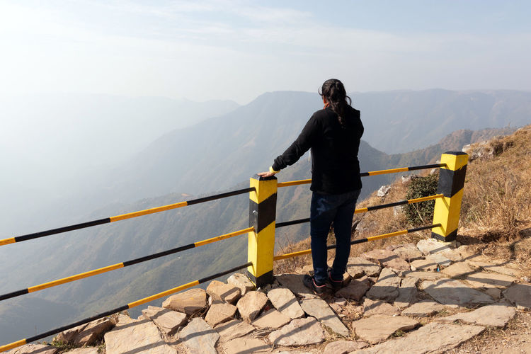 Full length of man standing on railing against mountain