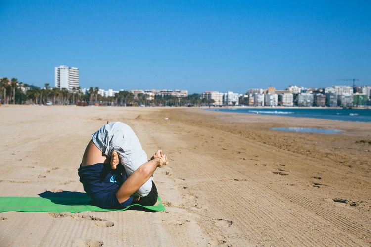 Full Length Of Man Performing Yoga At Beach By City Against Clear Blue Sky