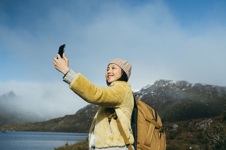 Low angle view of woman taking selfie against sky