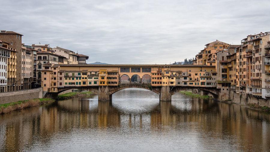 Ponte vecchio, bridge over river in florence against sky