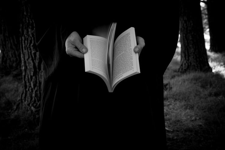 Midsection of person holding book in forest