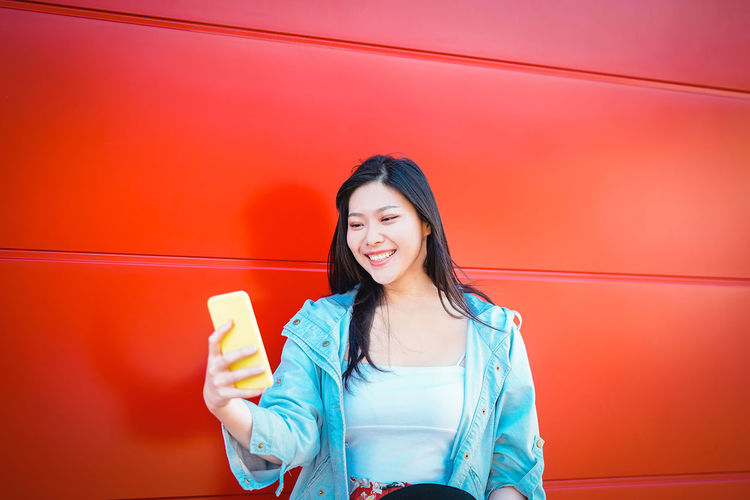 Smiling Young Woman Taking Selfie From Mobile Phone By Red Wall