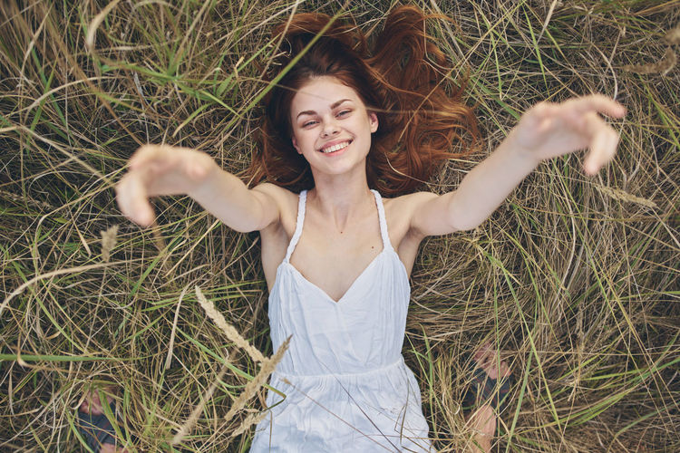 Portrait of smiling young woman lying on field