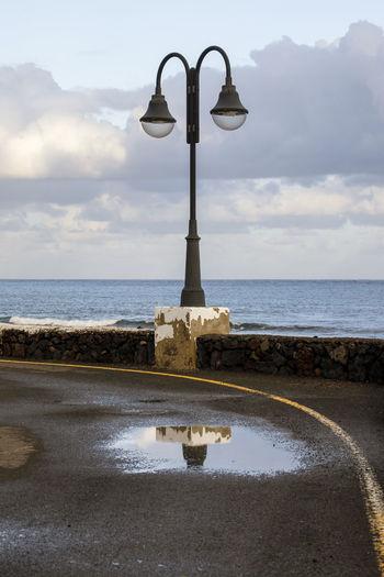 Street light on beach against sky