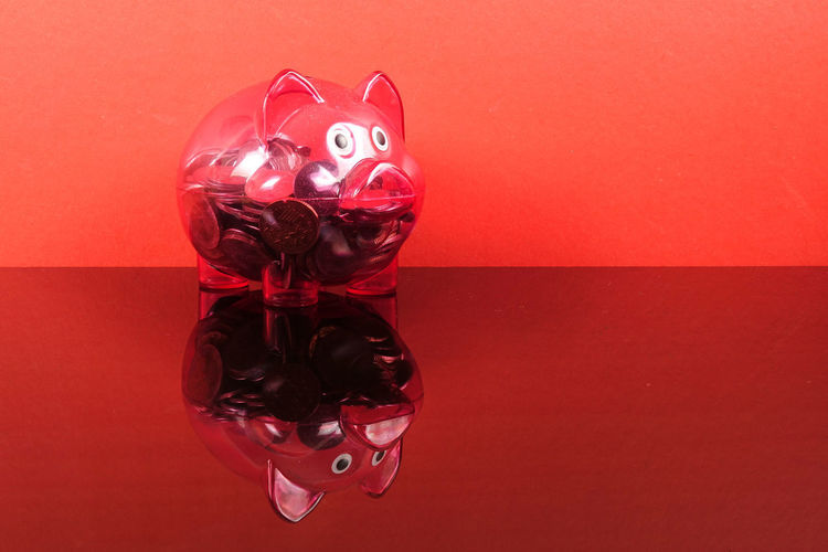 Saving concept with red piggy bank on red background. Piggy Bank Animal Representation Art And Craft Celebration Close-up Coin Colored Background Conceptual Photography  Creativity Glass - Material Heart Shape Holiday Indoors  Investment Mammal No People Piggy Bank Red Representation Saving Concept Shiny Still Life Table Toy Wall - Building Feature