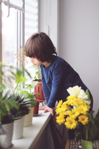 Boy by potted plants looking through window