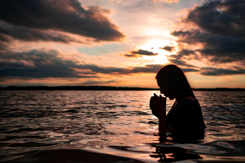 A young woman drinking from a mug while sitting in a lake at sunset
