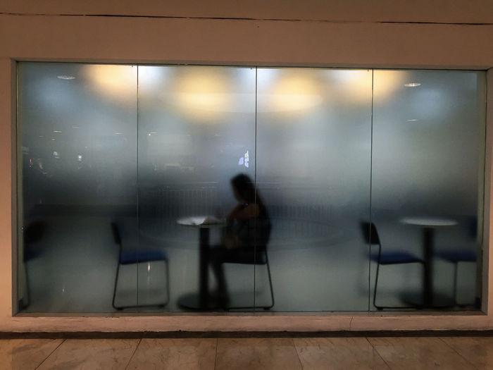 People sitting in glass of room