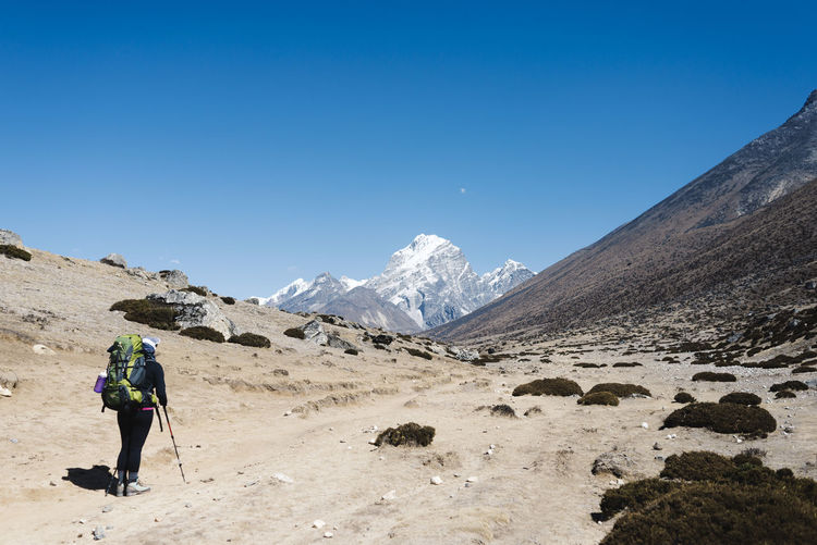 Full length of man on snowcapped mountain against clear blue sky