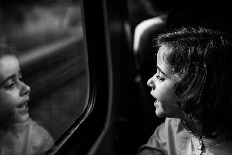 Cute Girl Looking Her Reflection In Car Window