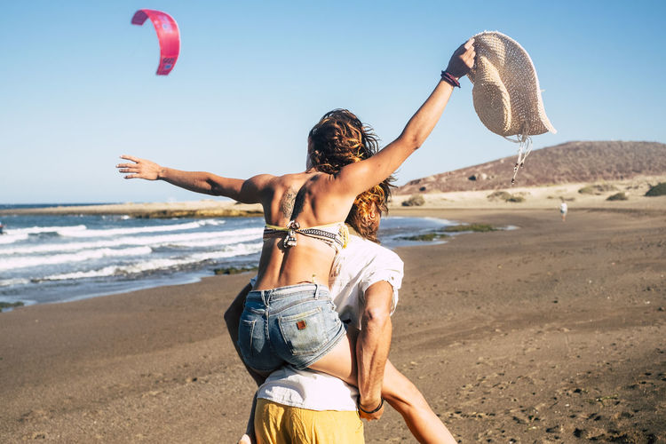 Rear view of man piggybacking woman at beach against clear sky